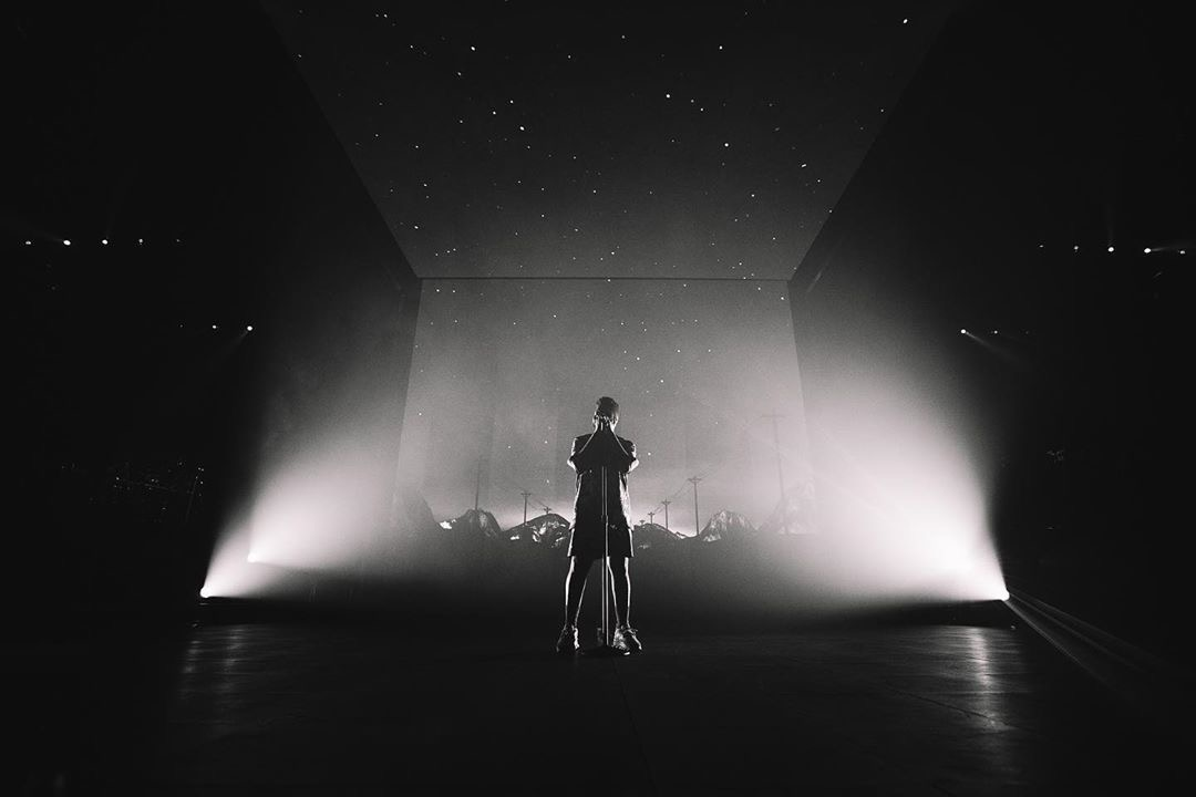 Khalid performing with white backlight.