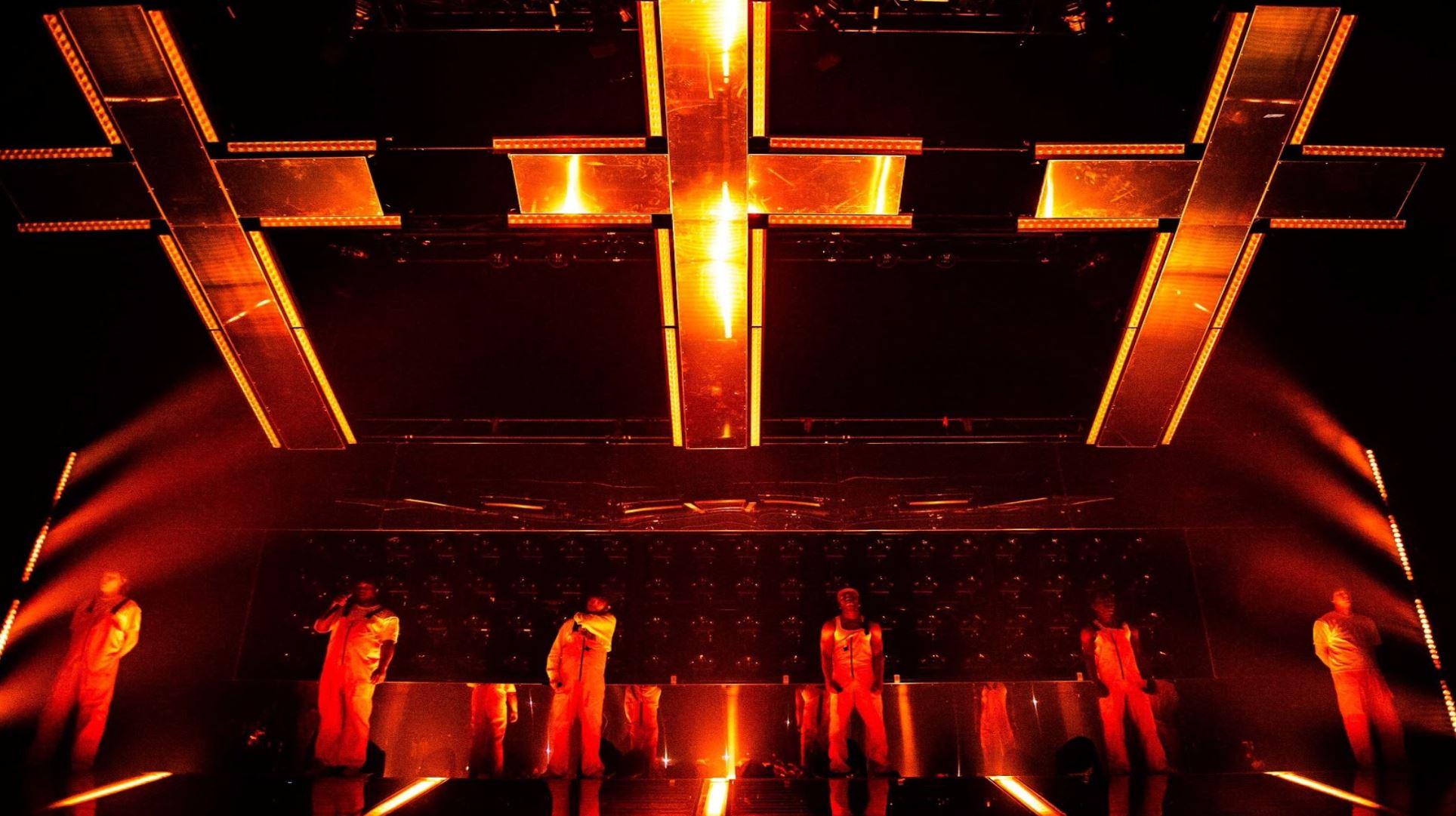 Brockhampton performing underneath orange crosses.