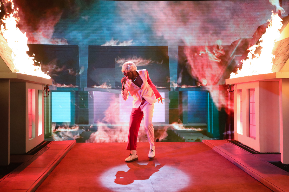 Tyler the Creator performing on a tilted stage at the Grammy Awards with fire on his left and right.