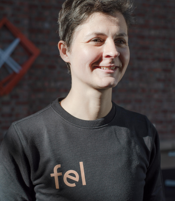 Foto van An Soenens die een zwarte pull draagt met het fel logo in het bruin op haar borst.
