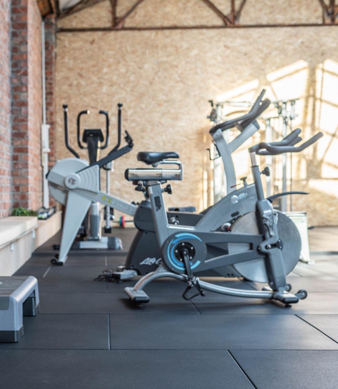Foto van fitnesstoestellen, verschillende fietsen.