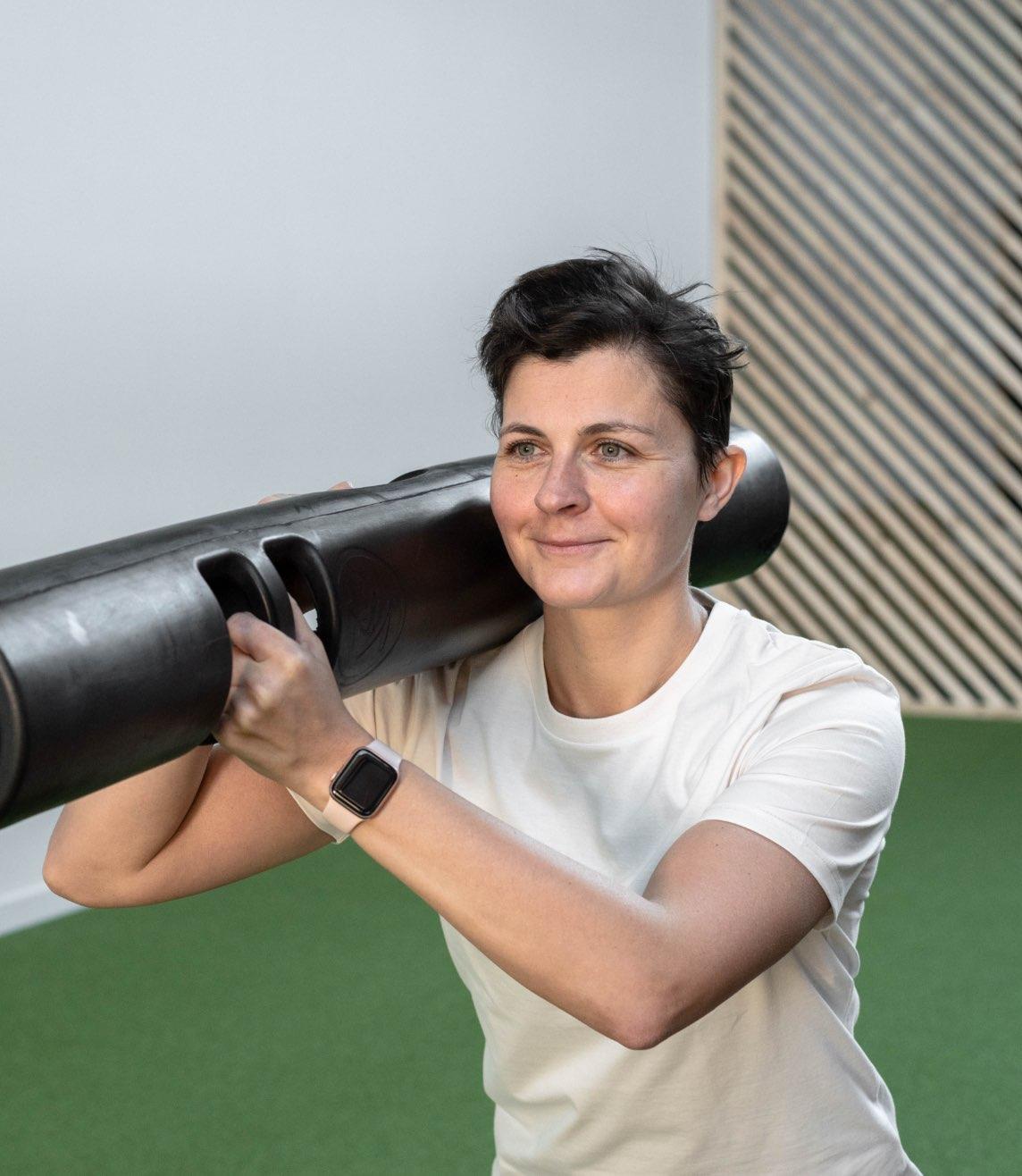 Foto van An Soenens die zwarte buis vast heeft op rechter schouder en oefening voor toont.