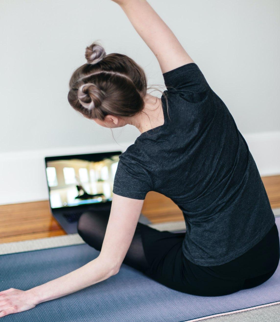 Foto van meisje dat voor laptop zit en sport.
