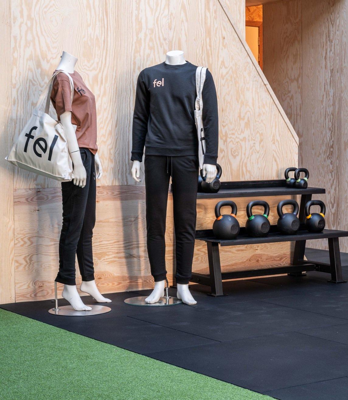 Foto van 2 mannequins met de kleren aan van FEL. De vrouwelijke mannequin, links in beeld, heeft een bruine t-shirt aan, zwarte jogging en draagt shopping bag. De mannelijke mannequin, rechts in beeld draagt een zwarte pull, zwarte jogging en draagt een tote bag.