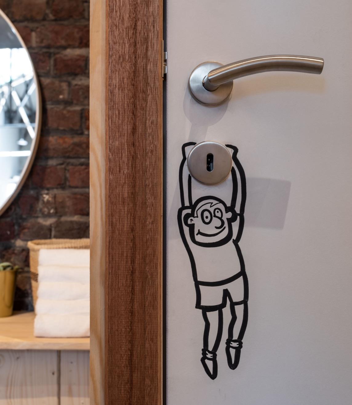 Foto van deur in de kleedkamer van FEL sportlocatie met een tekening op, een mannetje dat aan het sleutelgat hangt te bengelen.