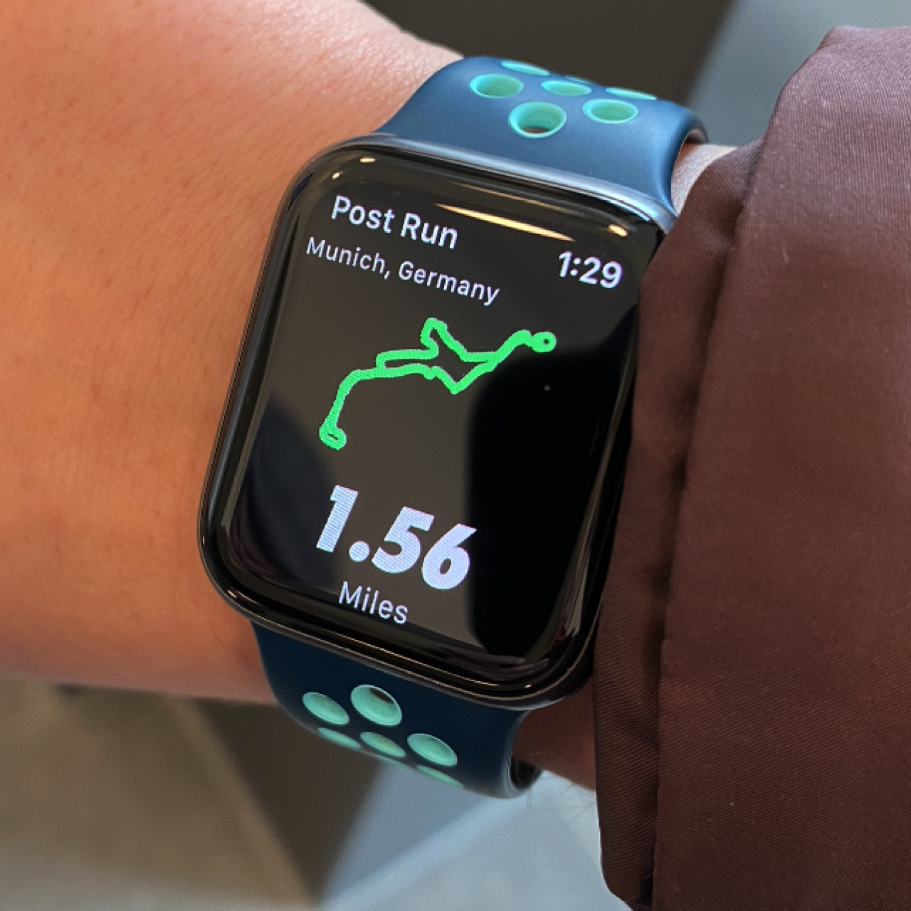 Photo of an Apple Watch on a person's wrist displaying a Nike Running summary screen