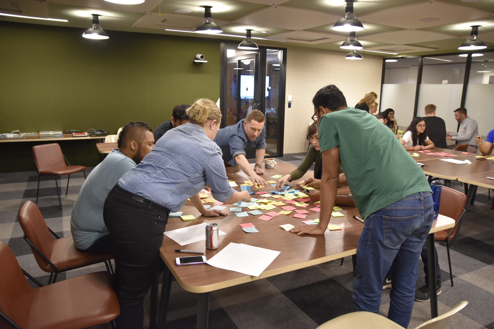Workshop participants standing and collaborating around a table with lots of sticky notes on the table.