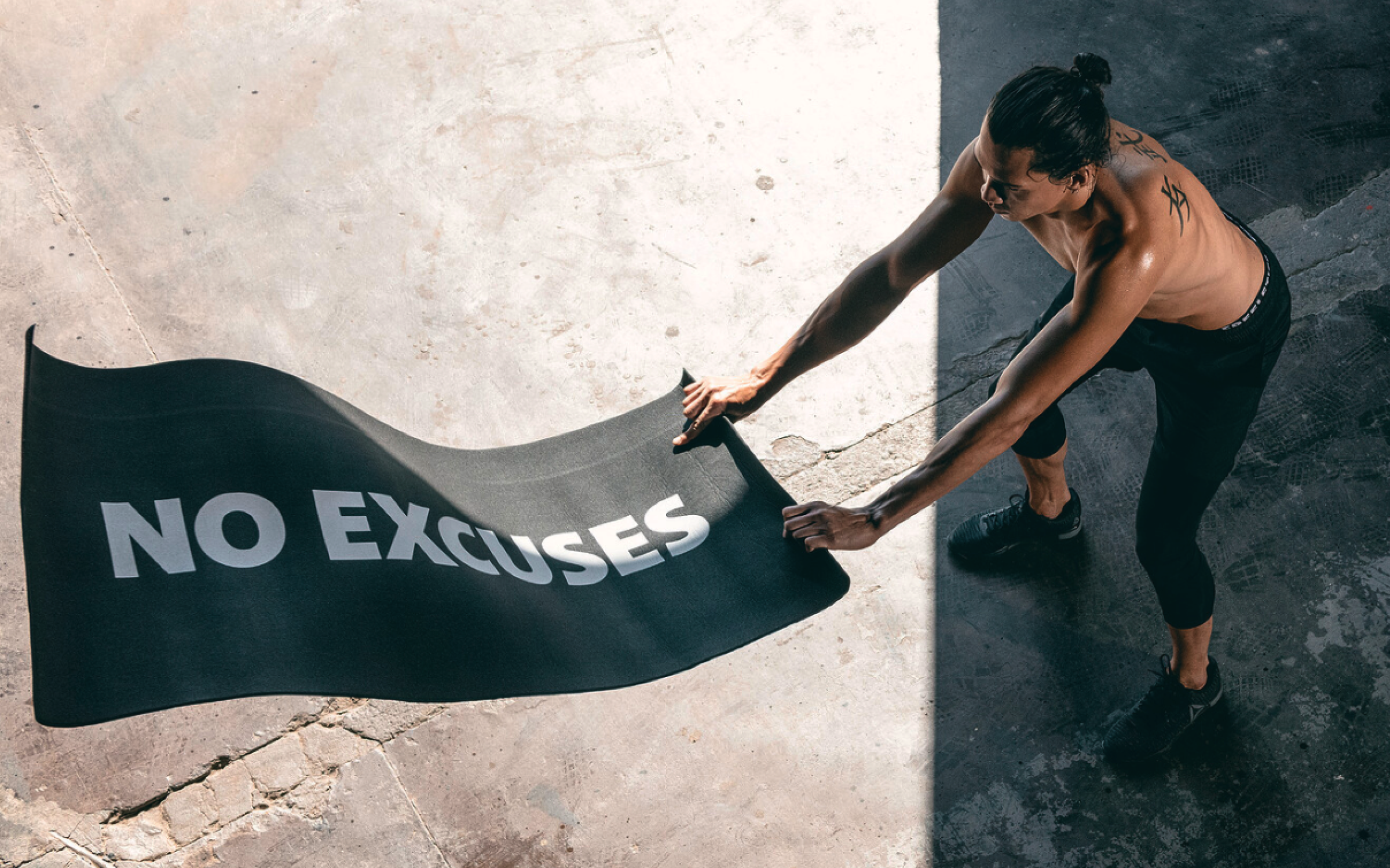 """Man unfurling a workout mat that reveals """"No Excuses"""" printed on the back"""