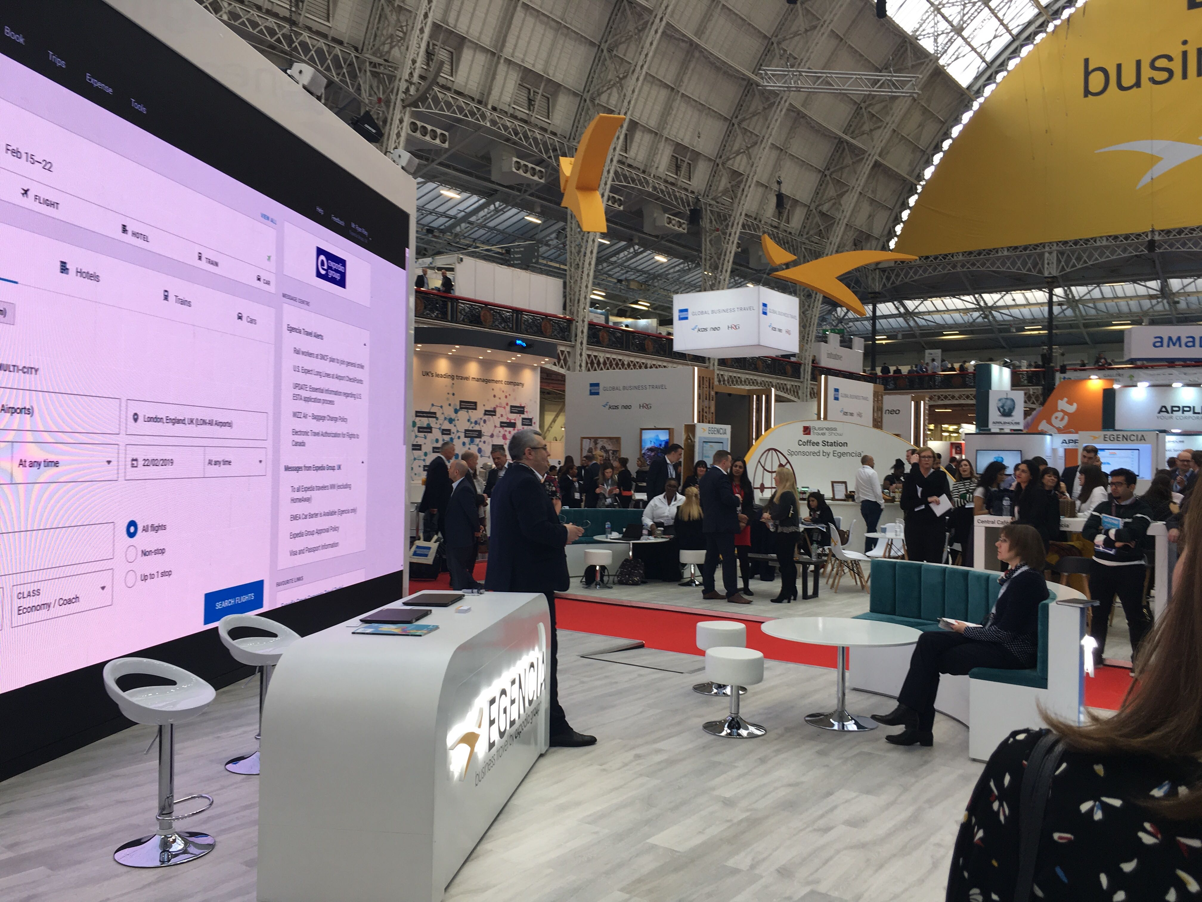 Image of a giant screen in a conference booth displaying the Egencia homepage at a large business travel conference in Europe. Lots of people milling around.