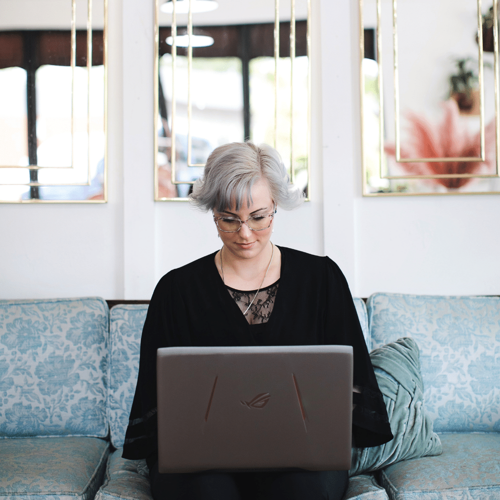 Anxiety therapist in Boise sits on a couch and types on a laptop.