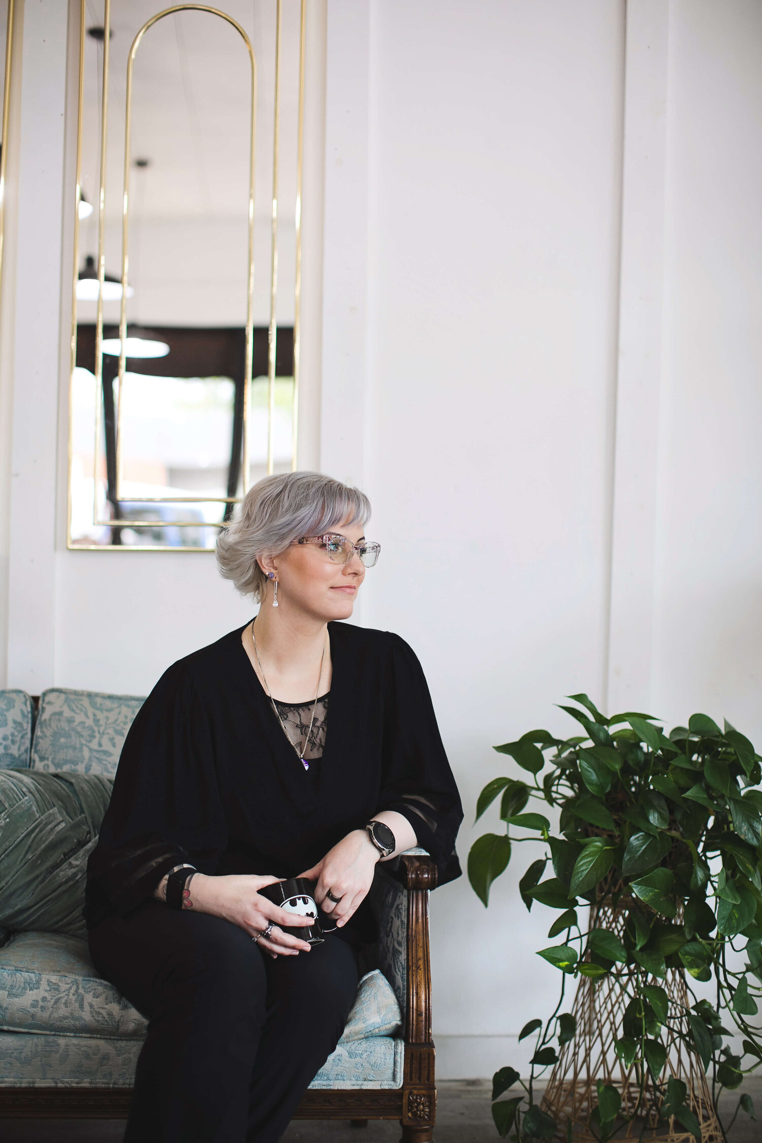 Anxiety therapist in Boise sits on a couch, with a coffee cup, looking off to the side.