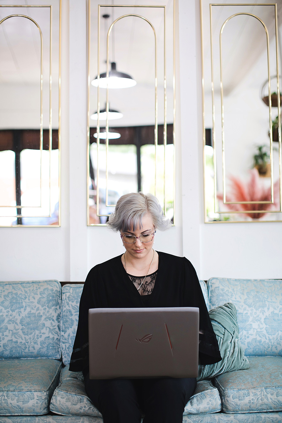 Online EMDR therapist sits on a couch and types on her laptop.