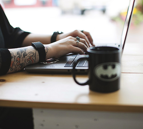 Online EMDR therapist sits at a desk and types at her computer while drinking coffee.