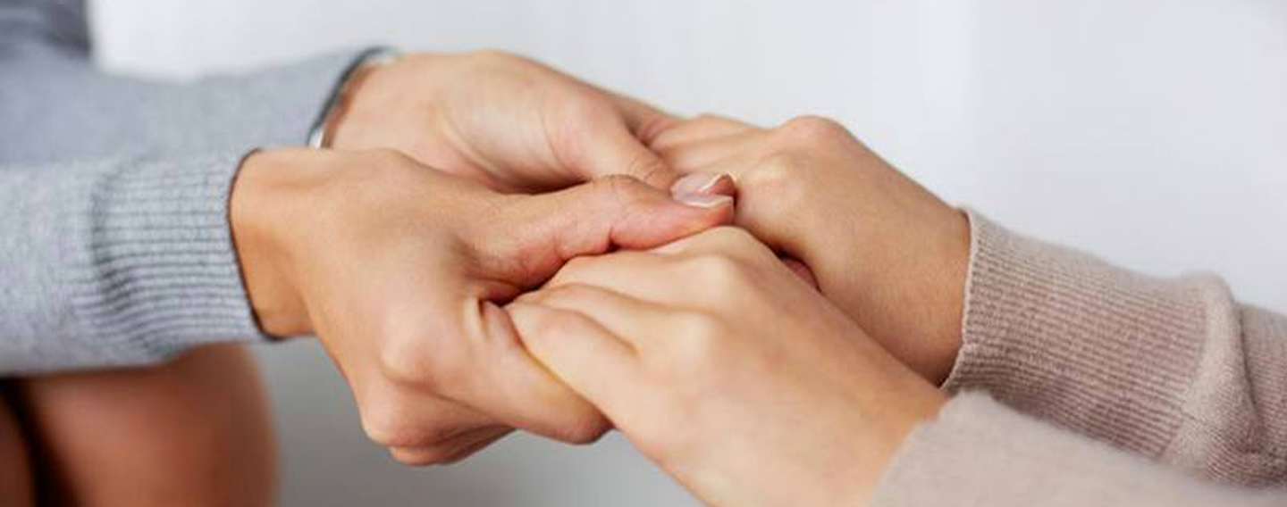 Two people holding each others hands in support
