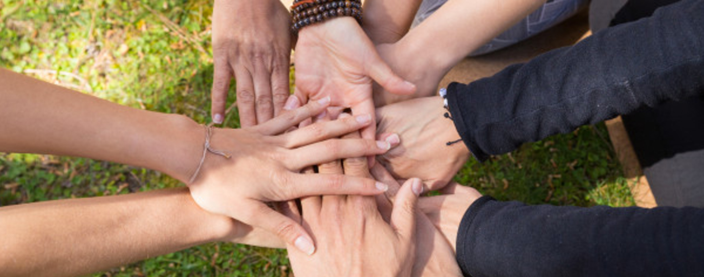 A group of people putting their hands in the middle to form a circle