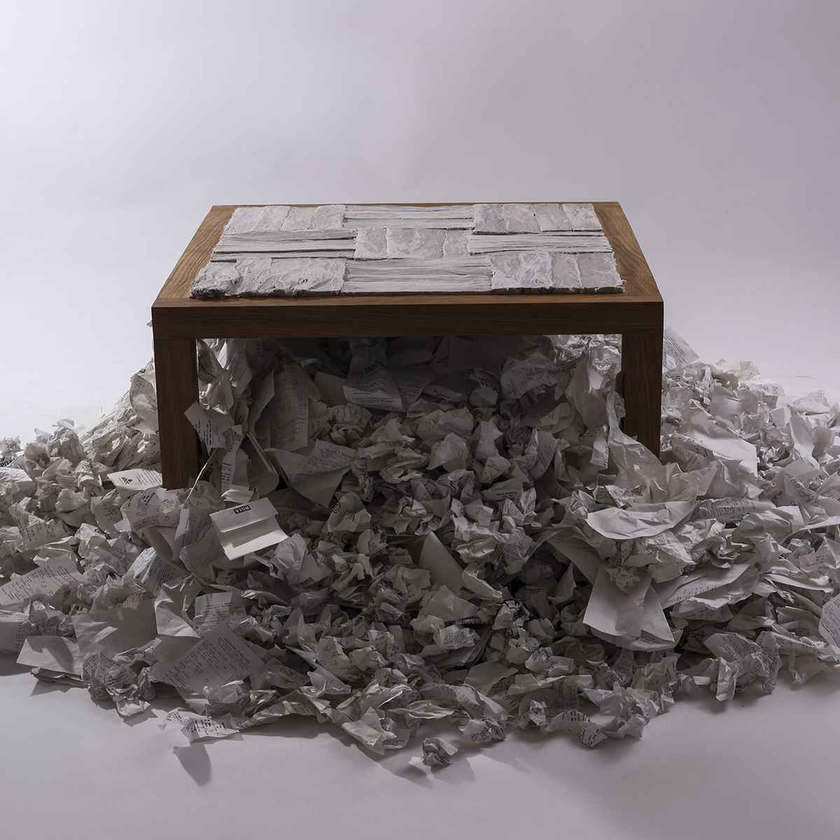 Stůl vznikl na téma Odpad a jeho dopad. Materiál, ze kterého jsem vycházela, je odkazem na globální produkci nadměrného množství odpadu, který nelze opakovaně využít. Použila jsem ke zhotovení nového deskového materiálu účtenky. Vylisovala je s vodou, čímž jsem docílila zajímavé struktury. Na samotnou desku je použito 12 622 účtenek, což je 6,311 kg směsného odpadu.