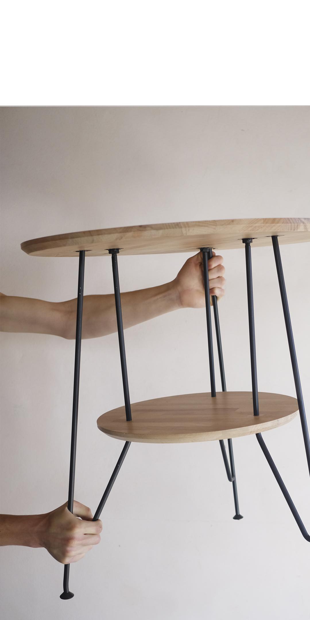Tři svařované nohy, procházející skrz spodní desku. Obě kruhové desky jsou vyrobeny z dřevěné spárovky, ošetřené transparentním lakem. Ocelová konstrukce v matném černém laku. Výška stolu 66,5cm, Průměr desky 60 cm, průměr spodní desky 40 cm.