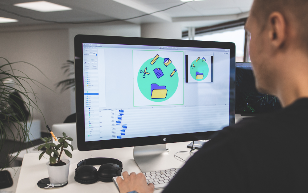 A designer working with design files on a computer.