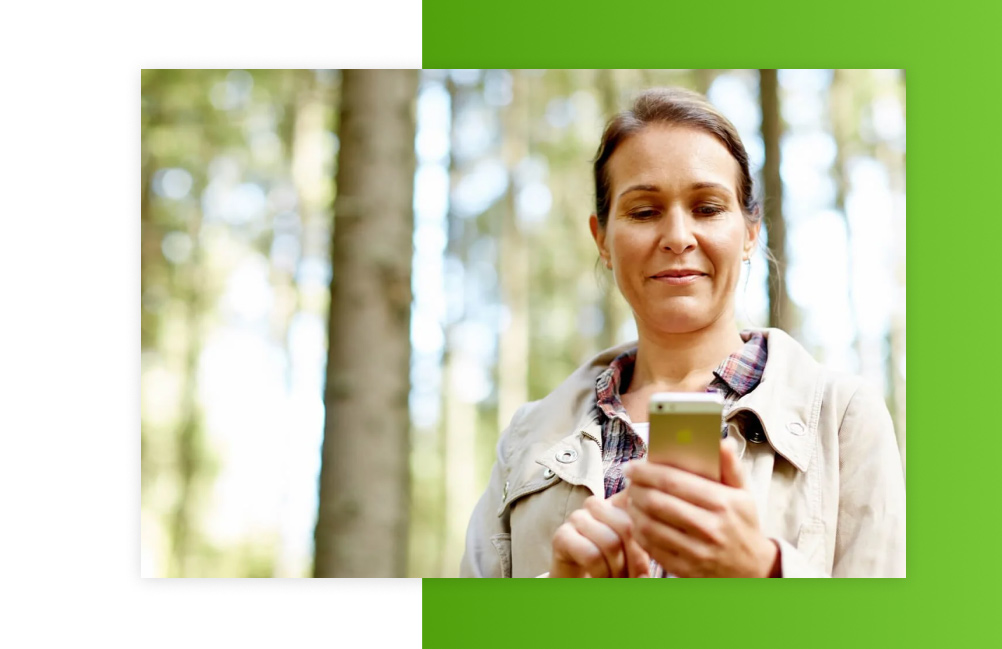 A woman using the UPM Metsä app. A forest in the background.