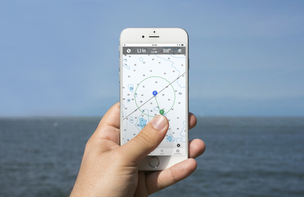 A person holding a phone in their hand. The phone displays the map view of the Loisto Mariner app.