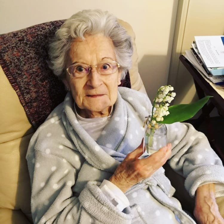 Une résidente en EHPAD avec un brin de muguet dans les mains