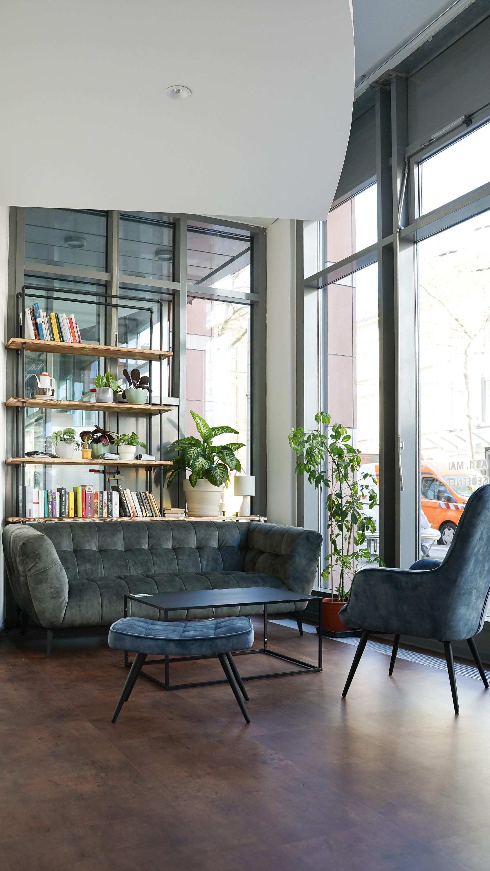 Eine Sitzecke, ein Bücberregal und einige Zimmerpflanzen