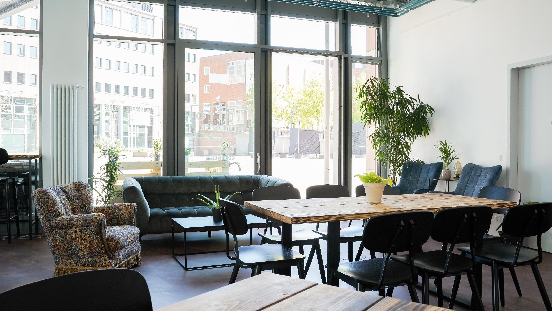 Der hintere Raum des Cafés, ein Sofa, mehrere Sessel und eine Tischgruppe