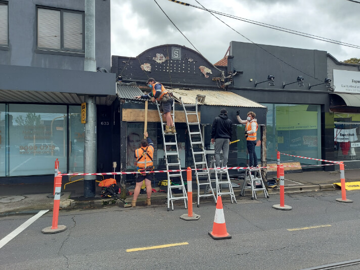 Supreme Roof Plumbers working on metal roof repair of a commercial building in Melbourne