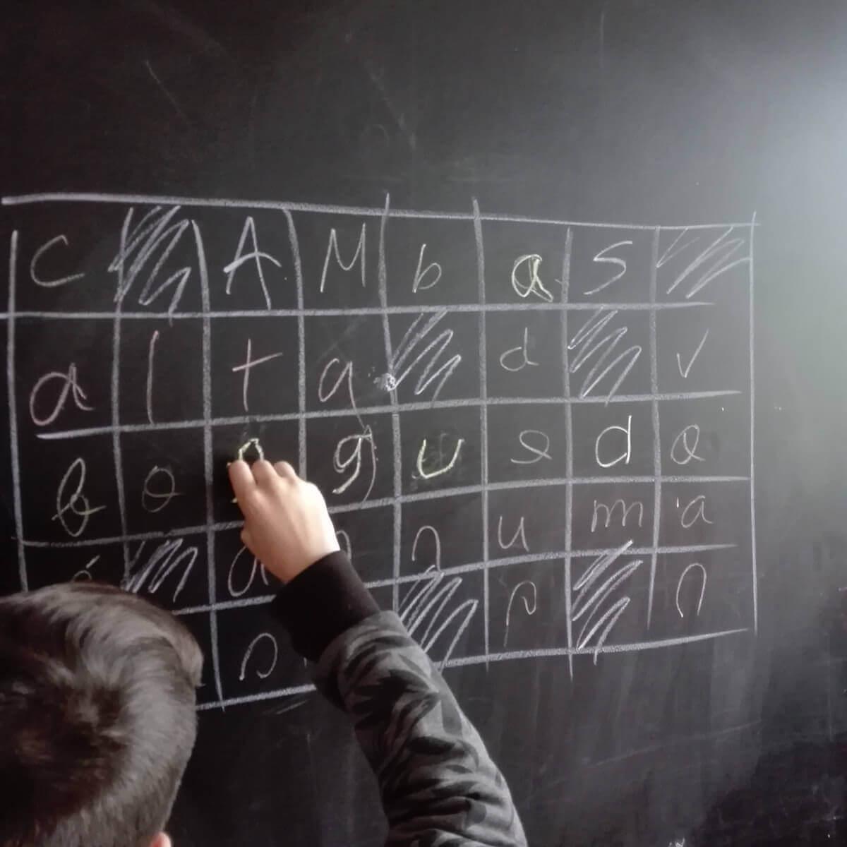 criança a fazer palavras cruzadas num quadro da escola
