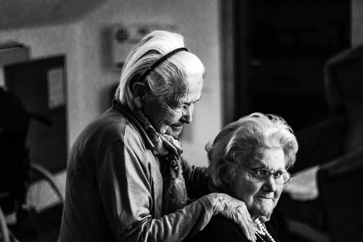 Uma idosa a massajar os ombros de outra idosa