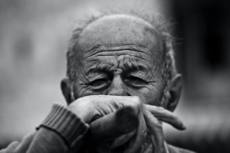 Close up de idoso com a mão na frente do rosto