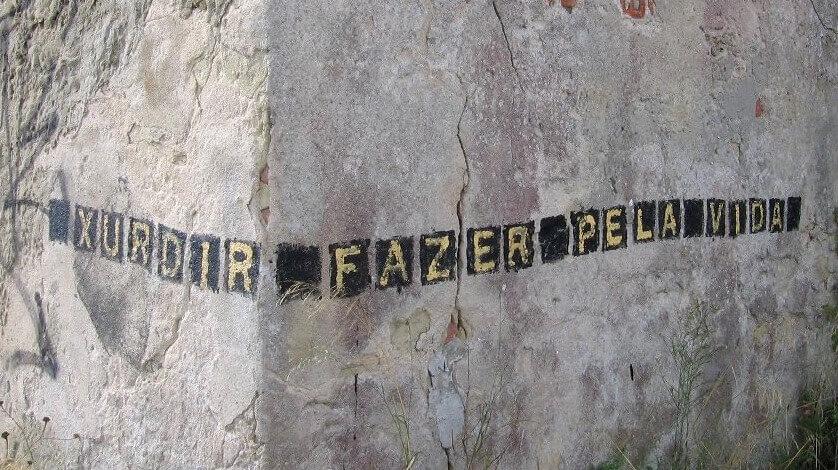 Palavra Xurdir escrita na parede|Pedra com a palavras Xurdir na Praia de Alburrica