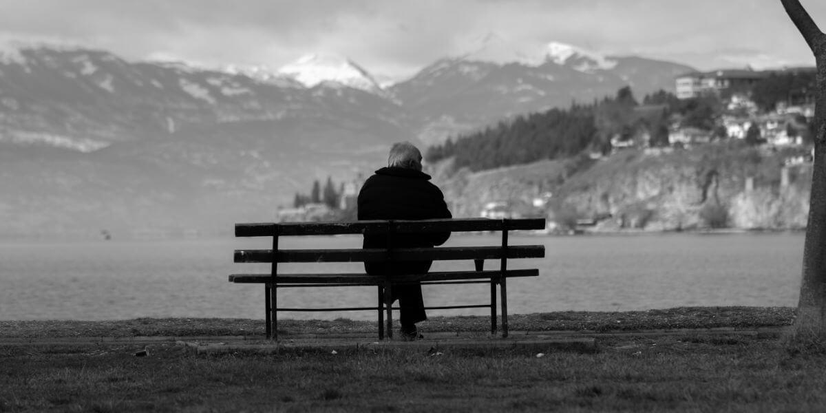 Idoso a sentado num banco de jardim a olhar o horizonte