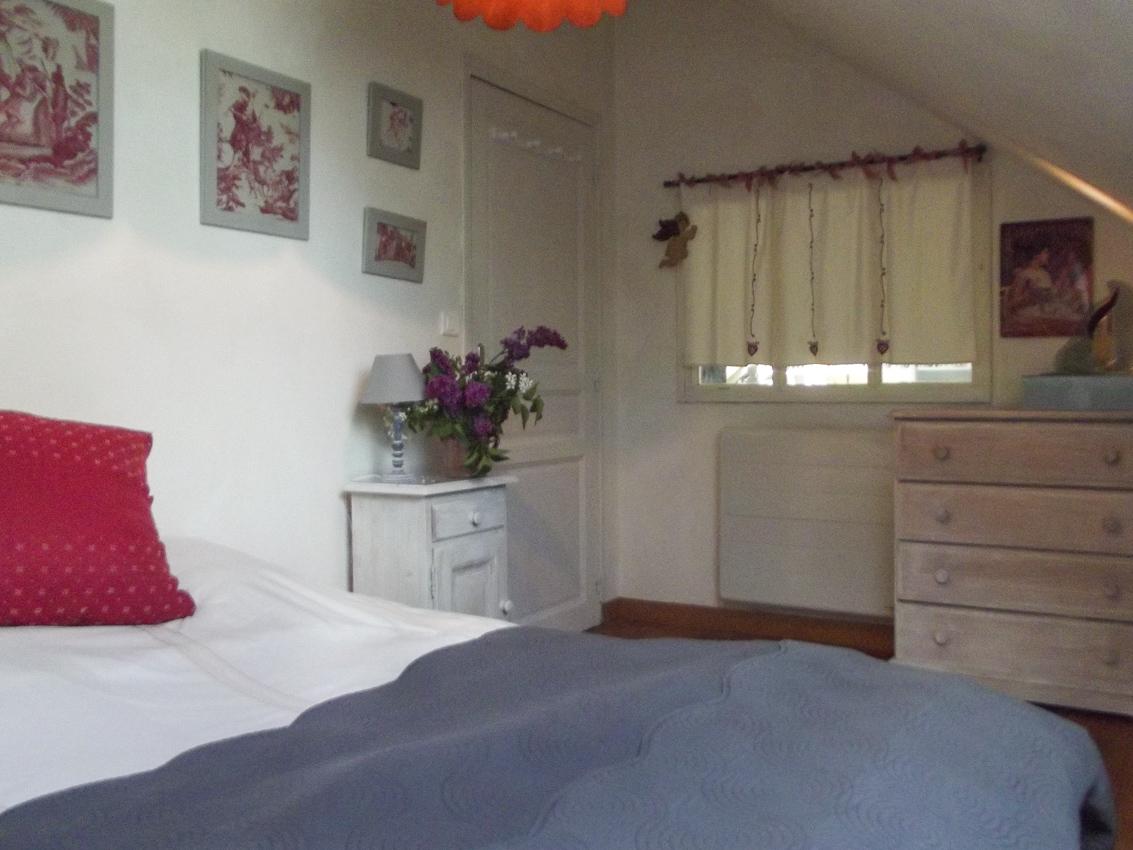 Le lit de la chambre lilas dans les tons de rouge