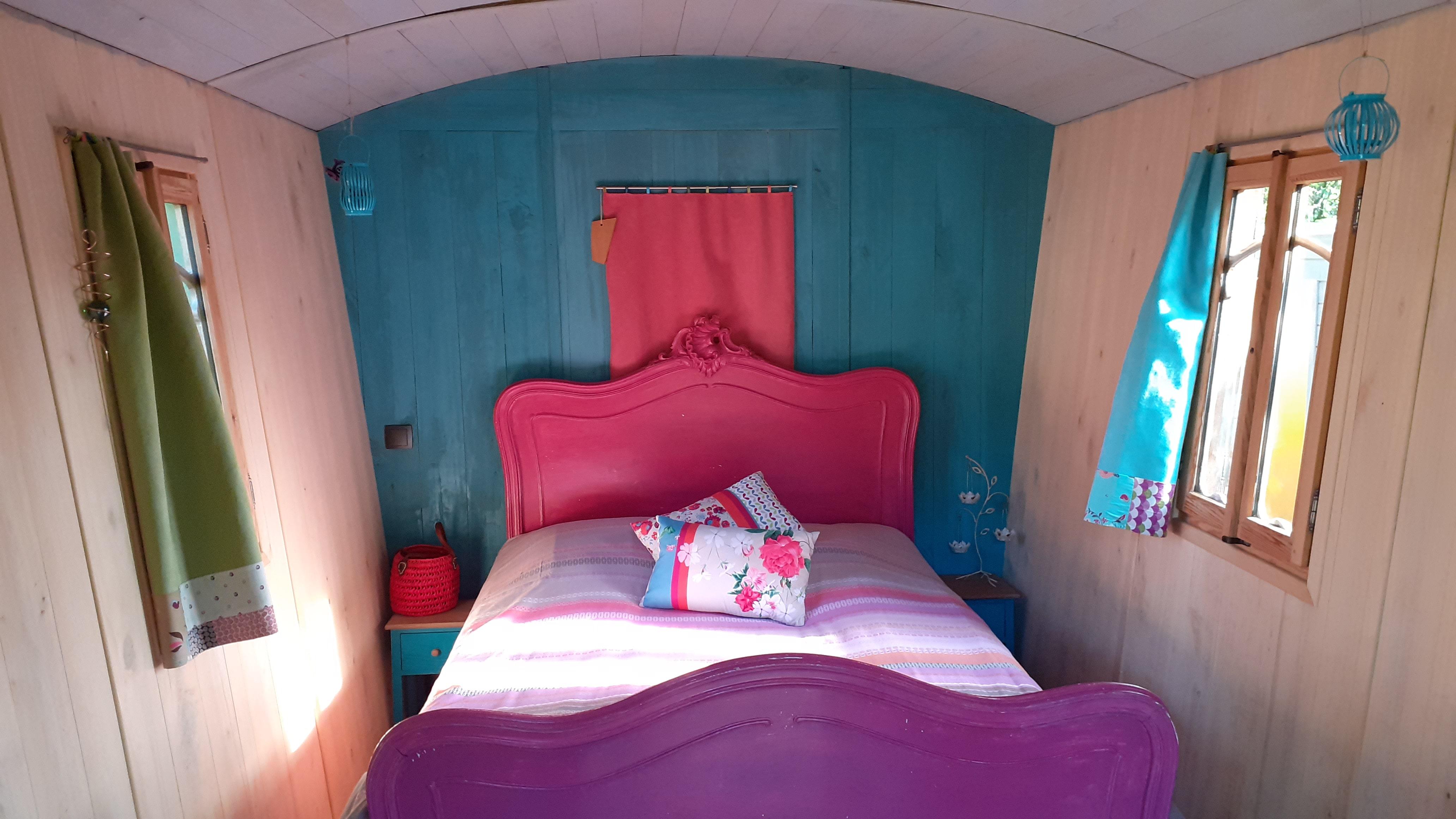 Le lit de la roulotte est dans les tons de violet.