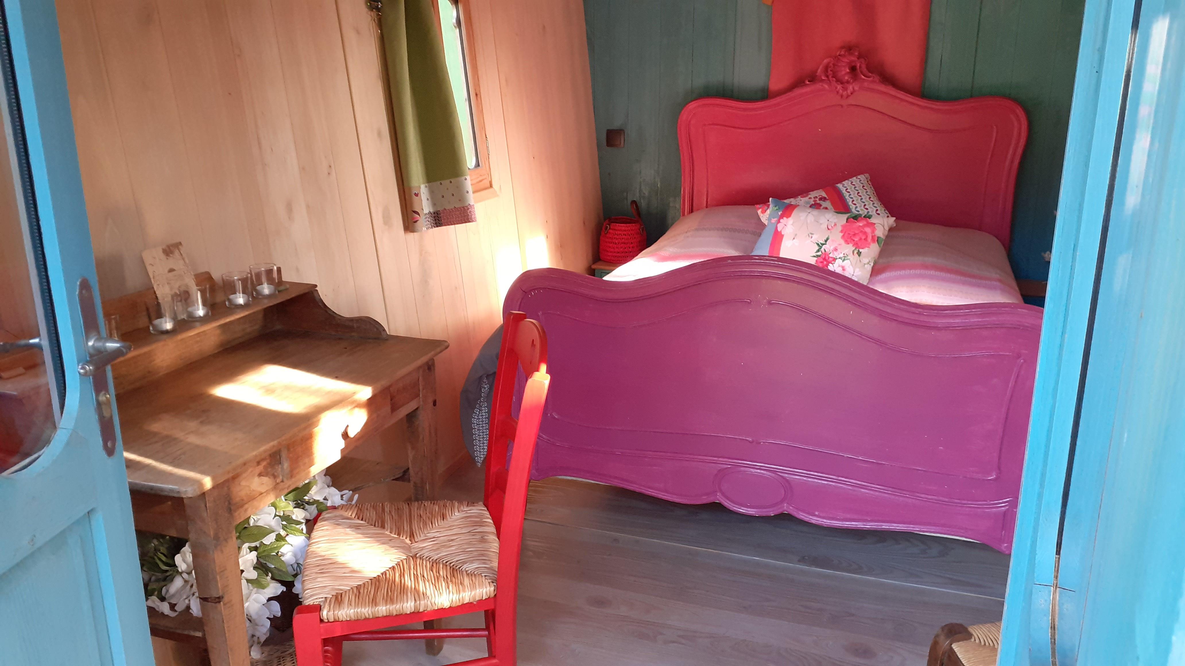 L'intérieur de la roulotte présente un lit et un bureau.