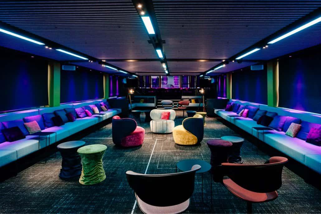 Lounge auf Schiff mit Sitzmöglichkeiten und farbigem Licht