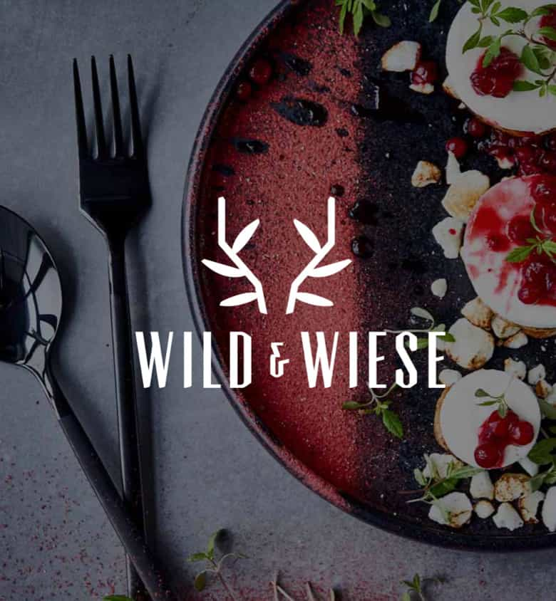 Wild & Wiese Logo auf einem Bild von einem Teller mit Speise