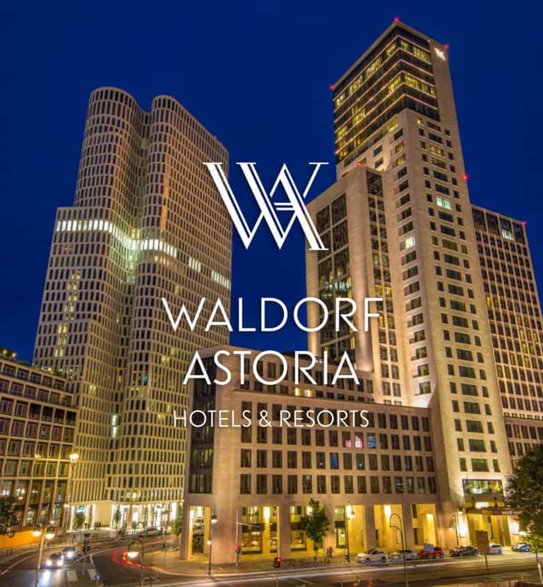 Waldorf Astoria Logo vor einem Bild von zwei beleuchteten Hochhäusern