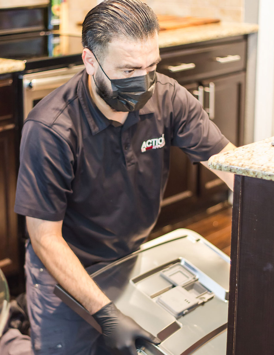 Benjamin repairing a dishwasher for Action Appliance Repair