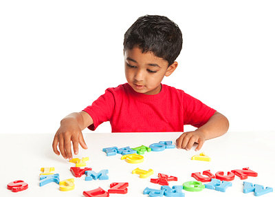 A little boy playing with colourful toy letters.