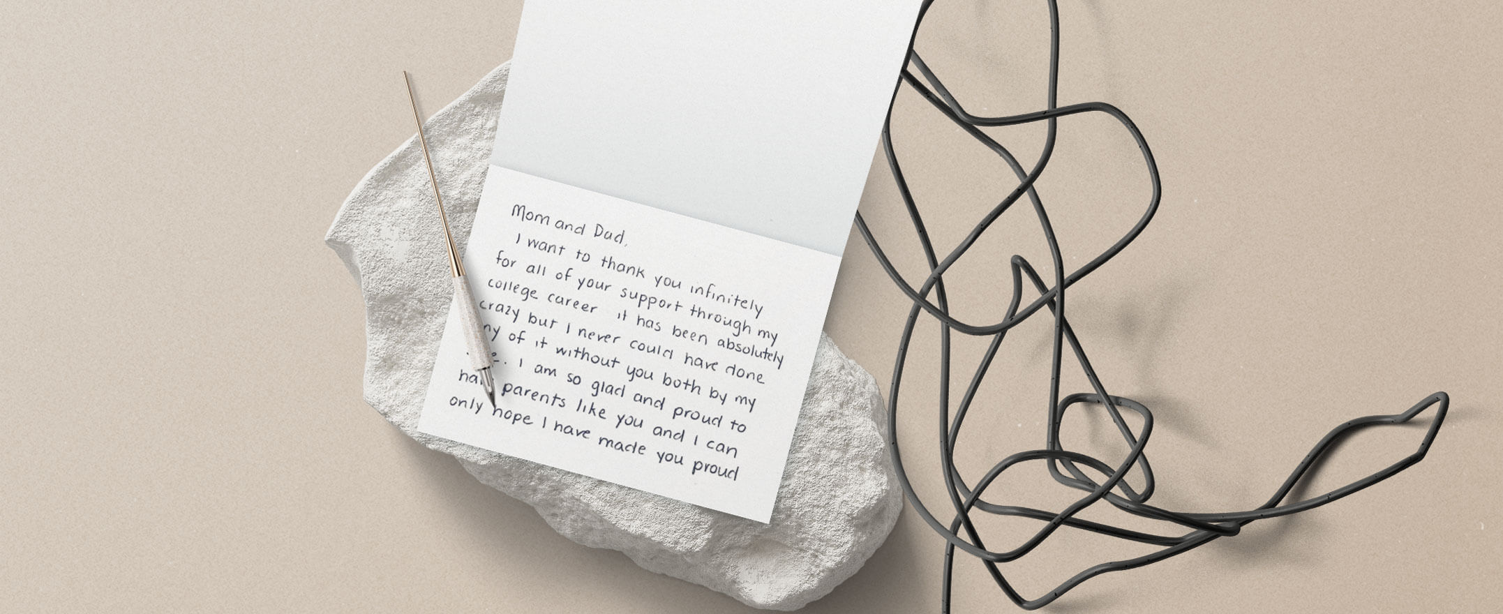 An open greeting card with a heartfelt message written on it. Placed on a rock, with a pen next to it.