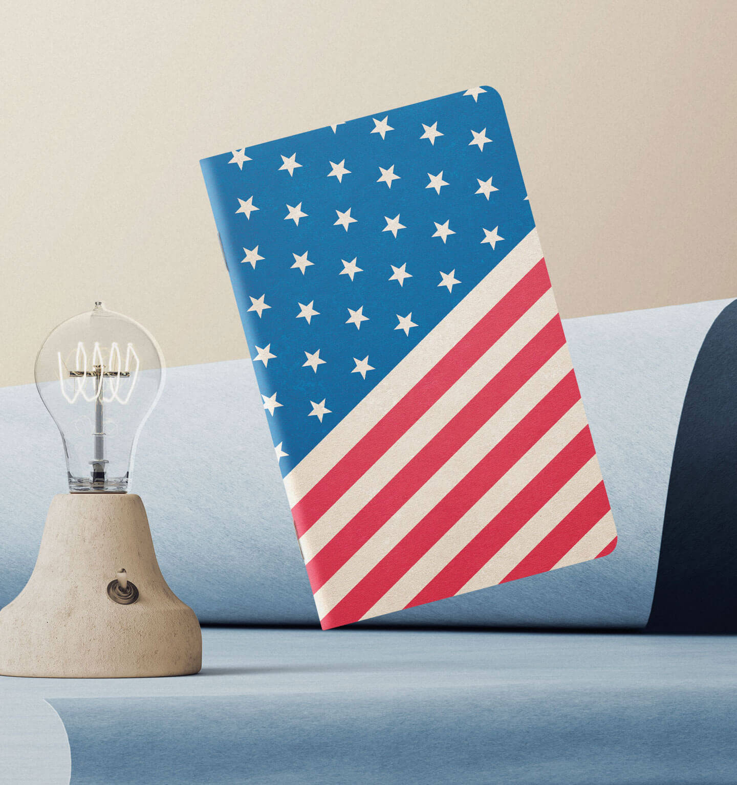 An American Flag notebook, next to a minialistic stone lamp.