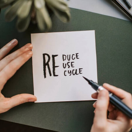 Zoomed in view of a hand writing 'Reduce, Reuse, Recycle' with a marker on a paper.