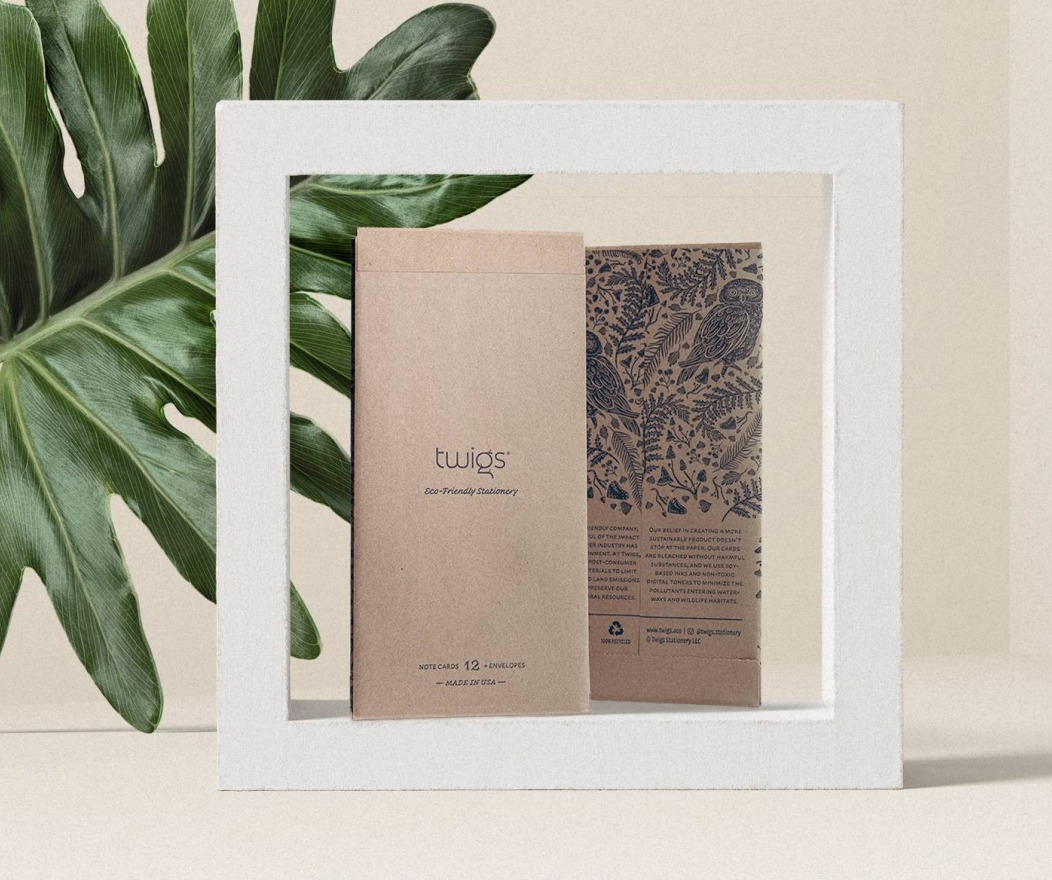 2 Twigs paper packages, front and back. Placed in a white frame in front of a green leaf.