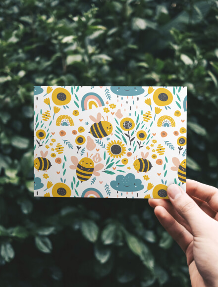 Hand holding a greeting card with cute bees and flowers illustrated on it, in front of a green bush.