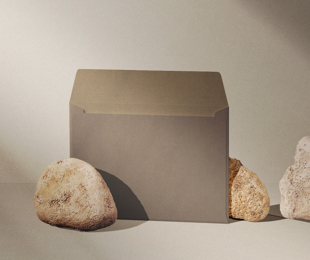 A brown opened envelope placed next to 3 small stones.