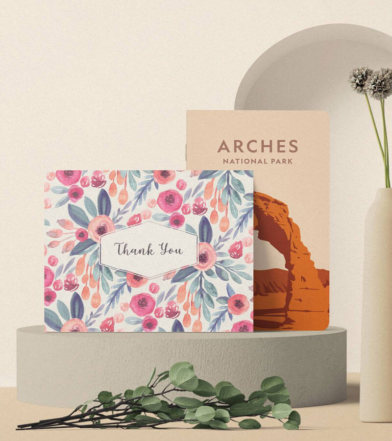 A thank you greeting card and arches national park notebook placed on a round cement with a branch with green leaves in front of it.