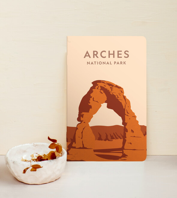 A notebook with Arches National Park illustrated on it, leaned om a white wall, and a small white vase next to it.