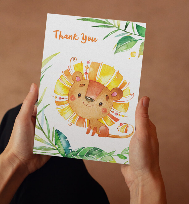 Hands holding a Thank You Eco Card with a Lion Illustrated on it.